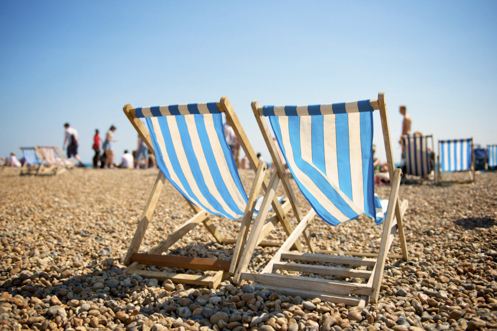 Two old fashioned striped deck chairs on pebble beach in the seaside resort of Brighton, East Sussex, England, UK