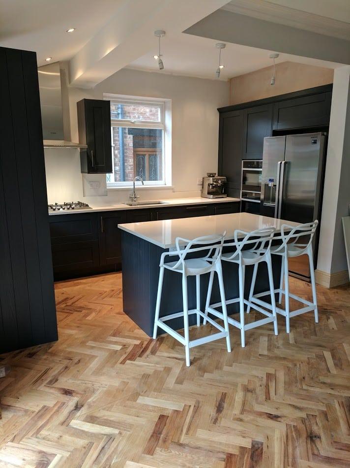 dark kitchen units with wood flooring. dark kitchen units with white worktops